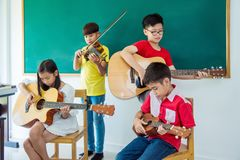 Children playing music instruments in music classroom Stock Image
