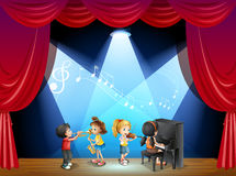 Children playing musical instrument on stage Royalty Free Stock Photos