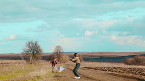 Children playing in nature with a kite. Two brothers run a kite. stock video footage