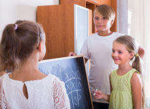 Children playing at Noughts and crosses. Positive children playing at Noughts and crosses indoors. Focus on girl Stock Photo