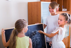 Children playing at Noughts and crosses. Three smiling children playing at Noughts and crosses at home. Selective focus Stock Photos