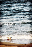 Children Playing in the Ocean Stock Images