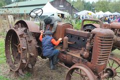 Children playing on old farm tractor Stock Photo