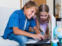 Children playing online on laptop Stock Photos