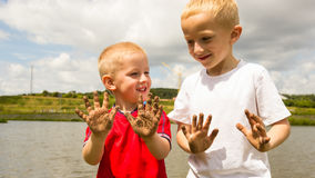 Children playing outdoor showing dirty muddy hands. Royalty Free Stock Image