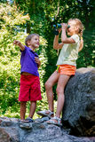 Children playing outdoors and having fun together with binoculars Stock Image