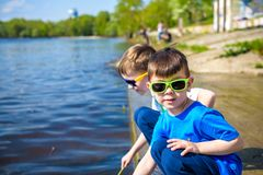 Children playing outdoors in nature: sitting on lake or river shore touching sand in clear water on warm summer or spring day. Stock Photo