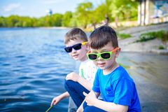 Children playing outdoors in nature: sitting on lake or river shore touching sand in clear water on warm summer or spring day. Royalty Free Stock Images