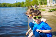 Children playing outdoors in nature: sitting on lake or river shore touching sand in clear water on warm summer or spring day. Brothers kid boy having fun royalty free stock photo