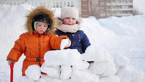 Children playing outdoors in winter. The child builds a wall of snow stones stock video footage