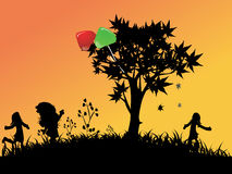 Children playing outside. Silhouettes of Children playing outside ,Balloons in the tree Stock Photography