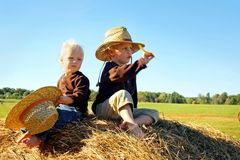 Children Playing Outside on Hay Bale. Two happy little boys, a 4 year old and his baby brother, are sitting outside on top of a large hay bale, wearing straw Stock Photography