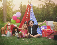 Children Playing Outside with Party Tent. Two children are playing outside dressing up as carnival people laughing at a circus party for an imagination or stock photos