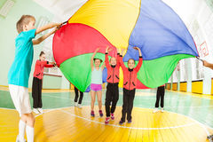 Children playing parachute games in sports hall. Group of happy 11-12 years old boys and girls playing parachute games in sports hall Stock Photos