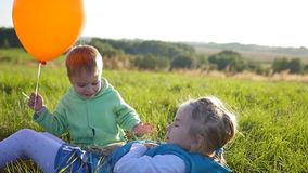 Happy children playing in the Park.Boy hugs and kisses his sister. Balloon. The laughter and smiles of children. Children playing in the Park. balloon. smile stock video