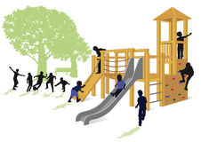 Children playing in a park. Silhouetted children playing on a climbing frame with slide in a park, white background Royalty Free Stock Photography
