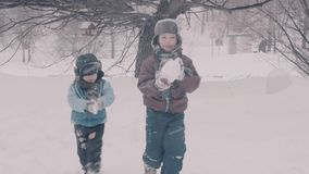 A children playing in the park in the snow. Portraits of two boys. A children playing in the park in the snow. Portraits of two boys outside in winter. 4K stock footage