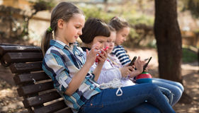 Children playing with the phone on bench outdoors Stock Image