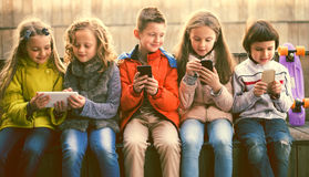 Children playing with the phone on bench outdoors Royalty Free Stock Image