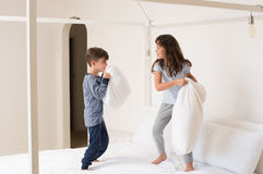 Children playing pillow fight. Siblings fighting using pillow in bedroom. Happy laughing brother and sister having a pillow fight in bedroom. Kids playing with royalty free stock photo