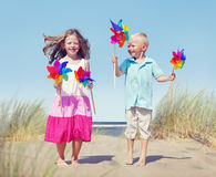 Children Playing Pinwheels by the Coastline Royalty Free Stock Images