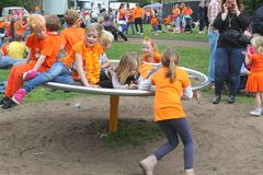 Children in orange clothes are playing at the playground at Kingsday (Koningsdag), Utrecht, Netherlands  Royalty Free Stock Photography