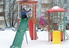 Children playing on playground in the yard. In the winter Royalty Free Stock Images