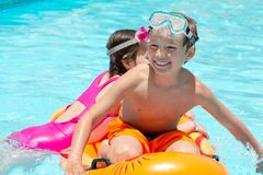 Children playing in pool. Happy young boy and girl playing on inflatable in swimming pool Stock Images