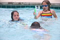 Children Playing in a Pool. Three girls playing together in a swimming pool stock photo