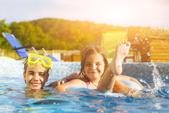 Children playing in pool. Two little girls having fun in the poo Royalty Free Stock Photos