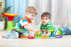 Children playing rail road toy in nursery Stock Photos