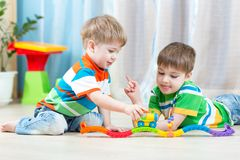 Children playing rail road toy in nursery Royalty Free Stock Photography