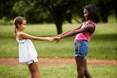 Children playing ring around the rosie in park. Two hispanic and african little girls playing ring around the rosie in public park and holding hands stock photography