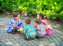 Children Playing Ring Around the Rosie. Two girls and two boys are holding hands together in a circle all crouching down playing a game of ring around the rosie royalty free stock photos
