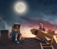 Children playing on the roof. Two little children playing astronauts. Children on the background of moon sky. Child boy in an astronaut costume and child girl Royalty Free Stock Photography
