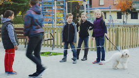 Children playing rubber band jumping game stock footage