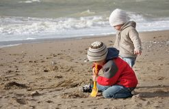 Children playing with sand on beach Stock Photo