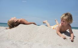 Children playing on sand beach Stock Photos