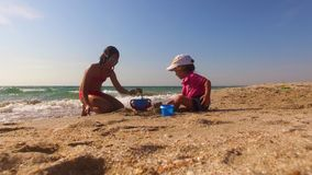 Children Playing With Sand On The Beach. Low angle shot of two children - little girl and little boy playing with sand on the beach putting it into toy bucket stock video footage