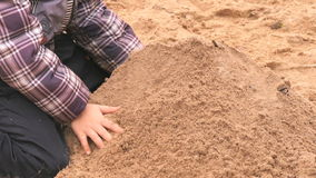Children playing with sand in outdoor sandbox. Children playing with sand and learning how to make shapes in outdoor sandbox. Close-up stock video footage