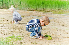 Children  playing in the sand on the shore of Lake Royalty Free Stock Image