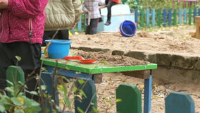 Children playing with sand on table in outdoor stock footage
