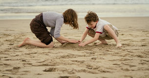 Children playing on sandy beach. Two young children building sandcastle on beach with sea in background Stock Image