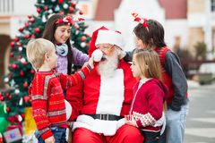 Children Playing With Santa Claus's Hat Stock Photos