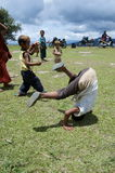 Children playing on the school field working on the headstands Stock Images