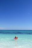 Children playing in sea. Two little children having fun in the sea (ocean), clear blue sky and water Stock Image