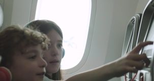 Children playing with seat back touchscreen devices on a plane stock video