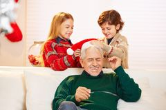 Children playing with senior man at christmas. Two children playing with senior men at christmas and putting christmas hat on his head stock image