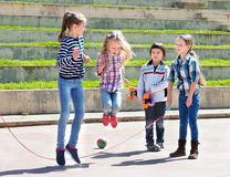 Children playing skipping rope jumping game Stock Photography