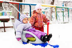 Children playing with sled and spade in snow Stock Photo